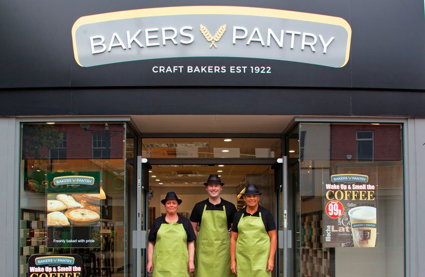 Bakers Pantry storefront with three workers stood in the doorway
